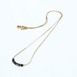 Collier noir et doré monté sur une chaîne fine dorée