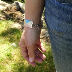 Photo portée du bracelet tissé aux couleurs pastel et aux motifs arrondis