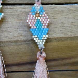 Collier aux couleurs pastels qui tombe sous la poitrine. Le tour de cou est en suedine, le tissage en perles miyuki, le tout terminé par un pompon couleur saumon