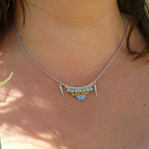 Collier porté pastel avec tissage sur métal et petites breloques en forme de pics