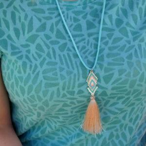 Photo porté du collier pastel qui tombe sous la poitrine. Le tour de cou est en suédine, le tissage en perles miyuki, le tout terminé par un pompon couleur saumon