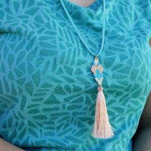 Photo porté du collier pastel tour de cou en suedine, tissage en perles miyukis terminé par un pompon couleur saumon