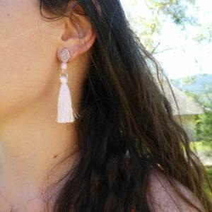 Photo porté des boucles d'oreilles tissées et terminées par un pompon rose pastel. Attache puce.
