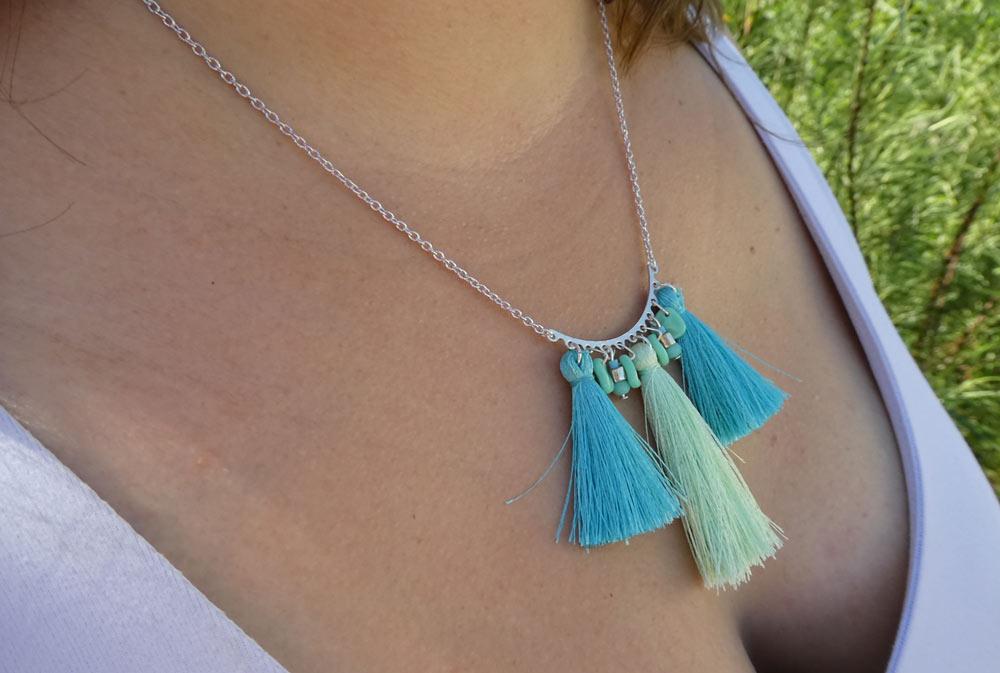 Photo porté du collier pastel pompons vert et bleu qui tombe juste au dessus de la poitrine, perles pétales, perles de bohème et perles miyuki