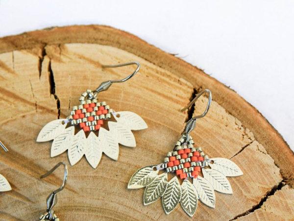 Boucles d'oreilles composées d'un tissage de perles miyuki orange et argenté assemblé avec un demi cercle en métal aux motifs feuilles